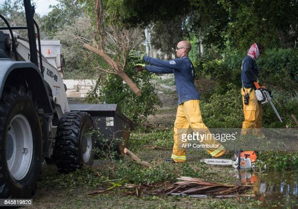 Workers clear fallen trees in Naples Florida on September 11 2017 after Hurricane Irma hit Florida Millions of Florida residents were without power...