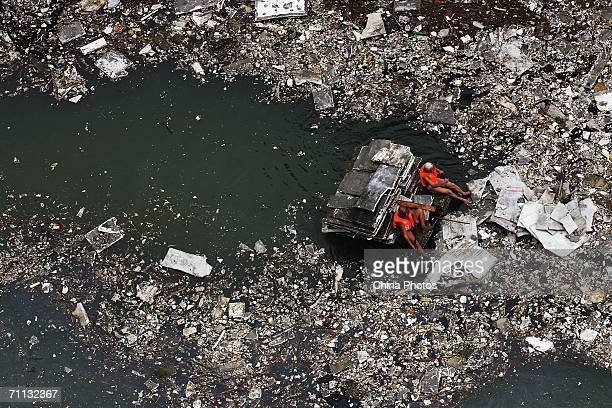Workers clear floating debris from the surface of the Yangtze River near the cofferdam protecting the justcompleted Three Gorges Dam on June 5 2006...