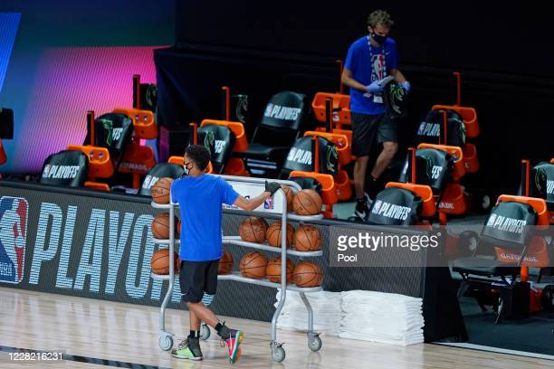 Workers clear items from the Milwaukee Bucks bench after the scheduled start of the first half of game five against the Orlando Magic in the first...