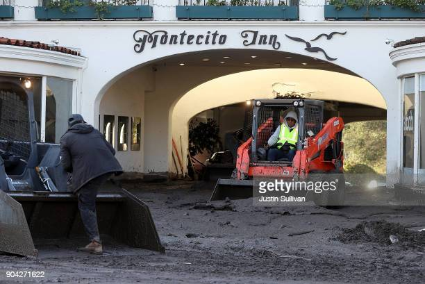 Workers clear mud from the parking garage at the Montecito Inn following a mudslide on January 12 2018 in Montecito California 17 people have died...