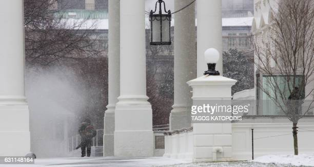 Workers clear off snow on the North Portico of the White House in Washington DC January 7 2017 / AFP PHOTO / Tasos KATOPODIS