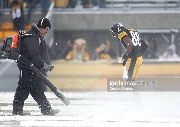 Workers clear snow from the field during a break in the action in the second quarter as Emmanuel Sanders of the Pittsburgh Steelers heads back onto...