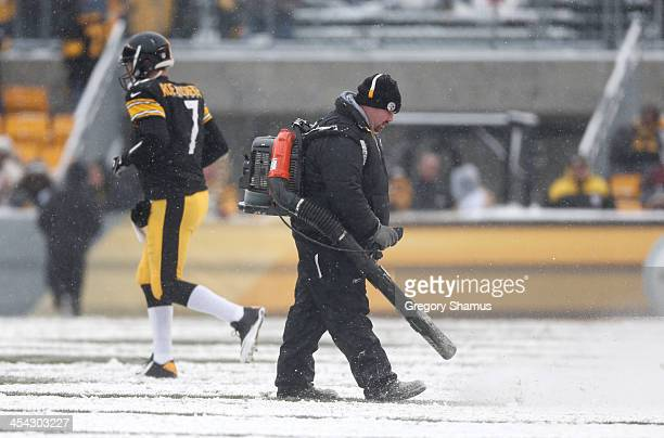 Workers clear snow from the field during a break in the action in the second quarter as Ben Roethlisberger of the Pittsburgh Steelersheads back onto...