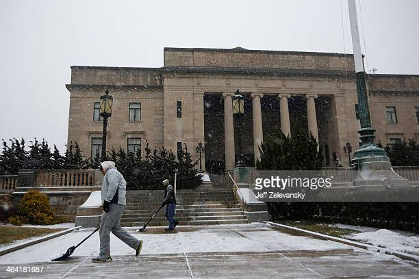 Workers clear snow from the Trenton War Memorial prior to New Jersey Gov Chris Christie being sworn in for his second term on January 21 2014 at the...
