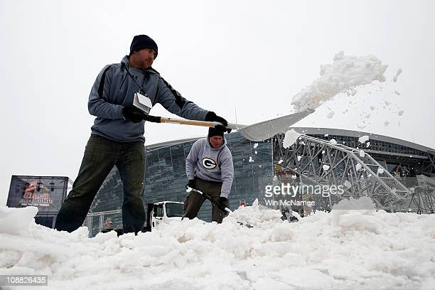 Workers clear snow outside the perimeter of Cowboys Stadium after a snowstorm hit the area February 4, 2011 in Dallas, Texas. More than four inches...