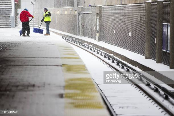 Workers clear the platform of the Massachusetts Bay Transportation Authority Massachusetts Avenue station during a snow storm in Boston,...