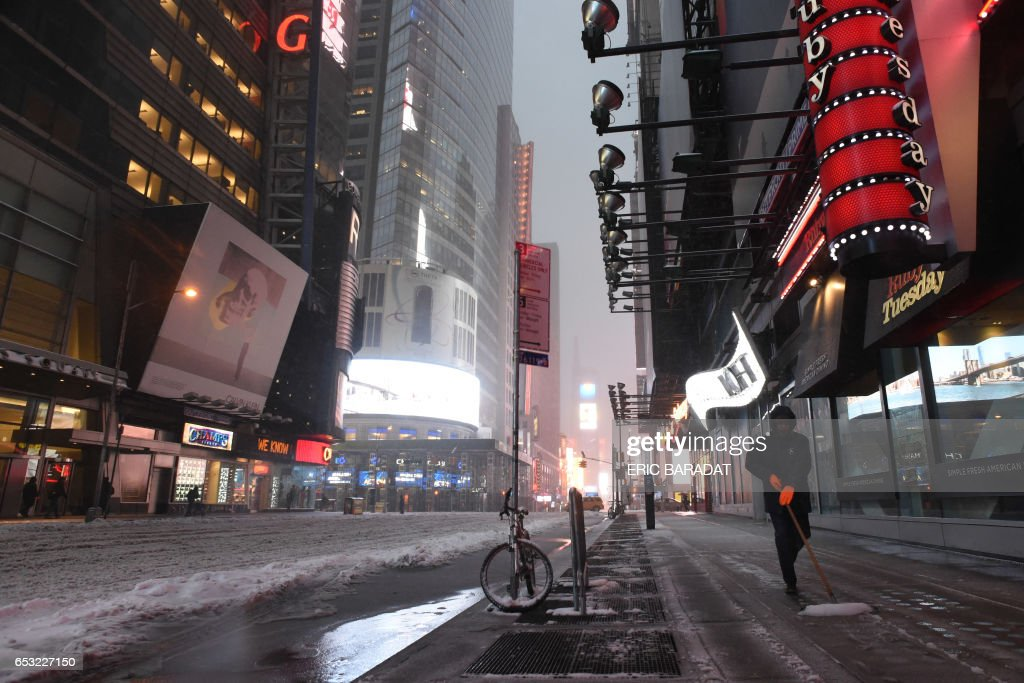 Workers clear the sidewalks from ice and snow in Times Square in New York on March 14, 2017. Winter Storm Stella dumped snow and sleet Tuesday across the northeastern United States where thousands of flights were canceled and schools closed, but appeared less severe than initially forecast. After daybreak the National Weather Service (NWS) revised down its predicted snow accumulation for the city of New York, saying that the storm had moved across the coast. PHOTO / Eric BARADAT