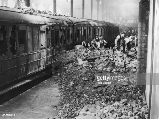 Workers clearing the debris after a German air raid on a British railway station during the Blitz, 9th September 1940.
