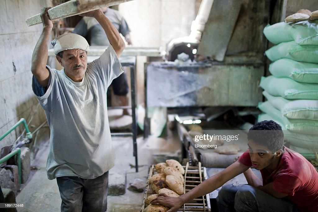 Workers collect freshly baked bread inside a bakery in Cairo, Egypt, on Monday, May 20, 2013. Egypt will curb wheat imports by 31 percent to 8 million metric tons in 2012-13, still enough to make it the world's biggest buyer, the U.S. Department of Agriculture estimates. Photographer: Shawn Baldwin/Bloomberg via Getty Images
