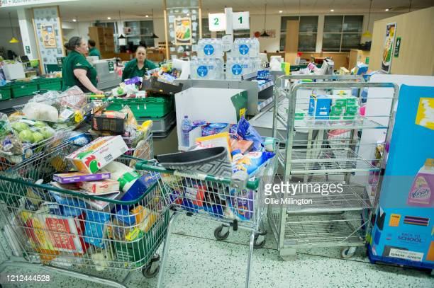 Workers collect items to restock the empty shelves in a London Morrisons store as panic-buying over coronavirus continues on March 14, 2020 in London...