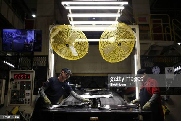 Workers collect metal parts while exiting a conveyor belt at the stamping plant of the Nissan Motor Co manufacturing facility in Smyrna Tennessee US...
