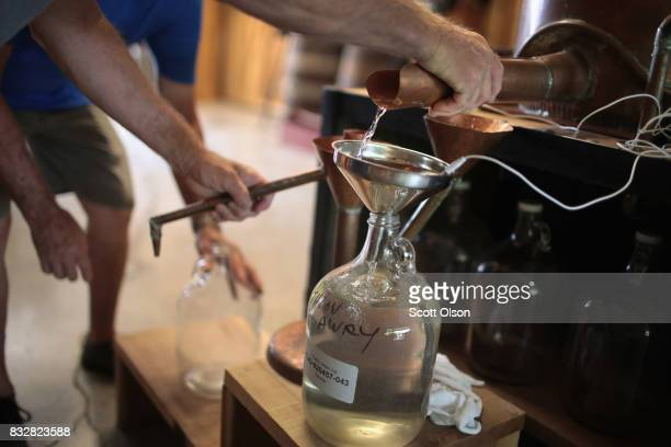 Workers collect moonshine as it runs from the still at Casey Jones Distillery on August 16, 2017 in Hopkinsville, Kentucky. To celebrate the upcoming...