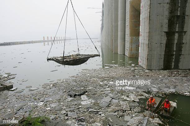 Workers collect rubbish in front of the Three Gorges Dam on June 5 2006 in Yichang of Hubei Province China Demolition experts finished setting the...