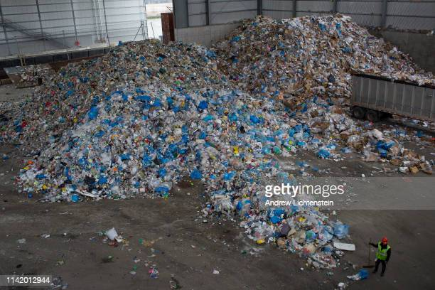 Workers collect the days recycled trash while New York City Mayor Bill De Blasio holds a press conference at a city recycling center processing plant...