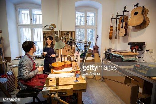Workers communicating in guitar workshop