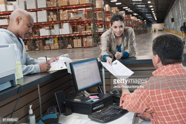 Workers completing paperwork in warehouse