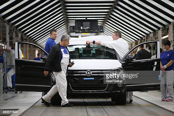 Workers conduct final inspections and prepare finished Volkswagen cars for transport at the end of the assembly line prior to a visit by Volkswagen...