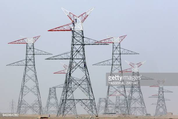 Workers conduct maintenance on an electrical tower southwest of Kuwait City on March 31 2018 / AFP PHOTO / YASSER ALZAYYAT