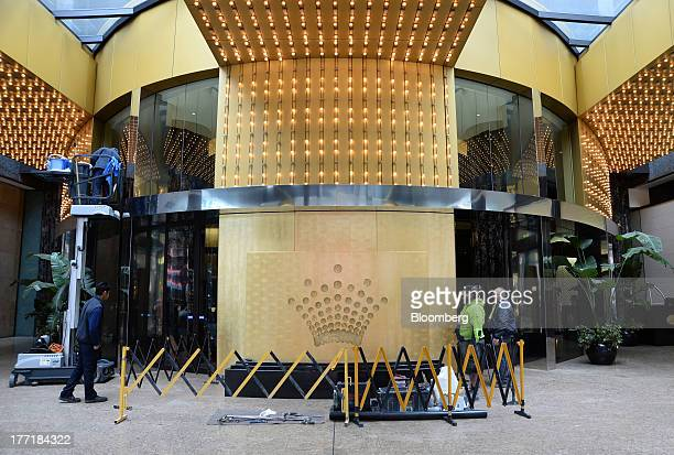 Workers conduct maintenance work near the Crown Ltd logo displayed outside the Crown Towers hotel part of the Crown Melbourne casino and...