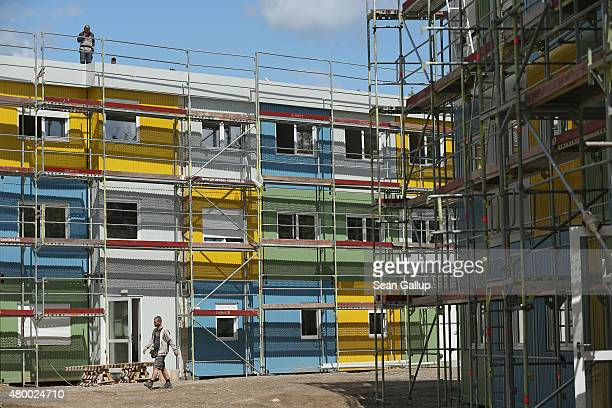 Workers construct a container facility in Zehlendorf district that will house refugees and asylum applicants on July 9 2015 in Berlin Germany This...