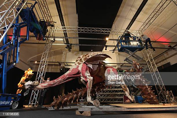 Workers construct a giant truss around a plastinated giraffe posed to look as if it is clinging to a tree in order to pull it upright at the Body...