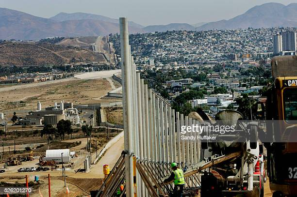 Workers construct a new section of border fence along the USMexico border in San Ysidro California New secondary border wall is being built to help...