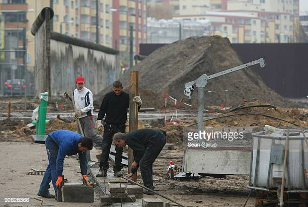 Workers construct an extension to the Berlin Wall memorial at Bernauer Strasse in front of a stillstanding section of the former Berlin Wall on...