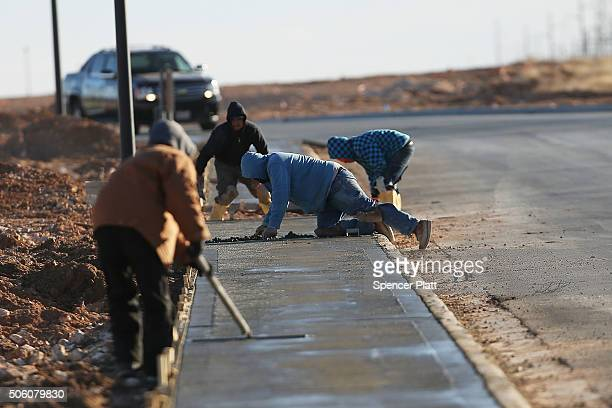 Workers construct new sidewalks in the Permian Basin oil field on January 21 2016 in the oil town of Midland Texas Despite recent drops in the price...