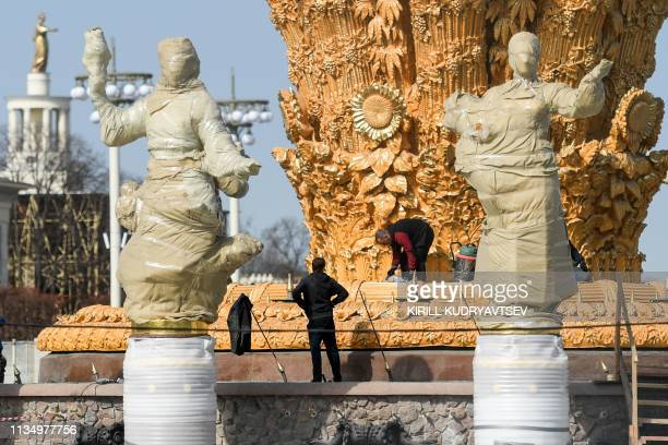 Workers construct the famous Druzhba Narodov fountain in the AllRussia Exhibition Centre a trade show and amusement park in Moscow on April 5 2019...