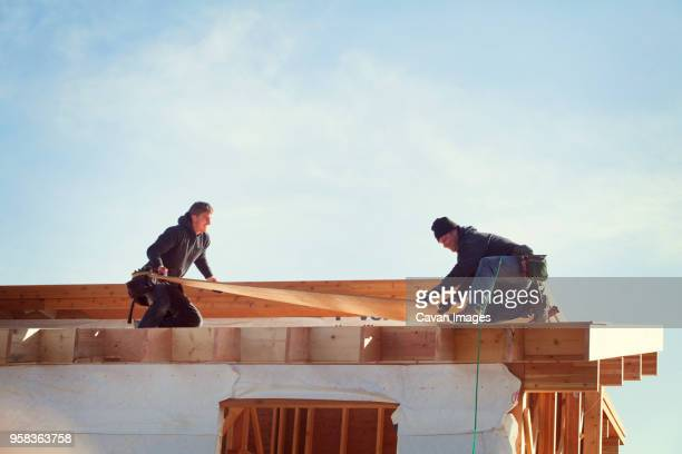 workers constructing roof beam against sky during sunny day - foundation make up stock pictures, royalty-free photos & images