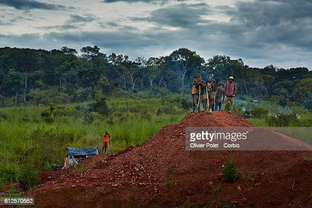 Workers contemplate the day's work upon arrival at site 28 March 2013 at the 7/7 diamond mining site near an Angolan village not far from the...