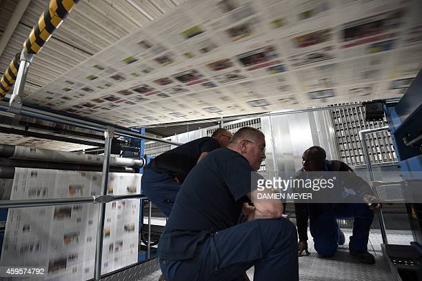 Workers control the process of the new rotary printing press during a test phase at French media OuestFrance headquarters in the western city of...