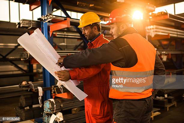 Workers cooperating while looking at blueprints in aluminum mill.