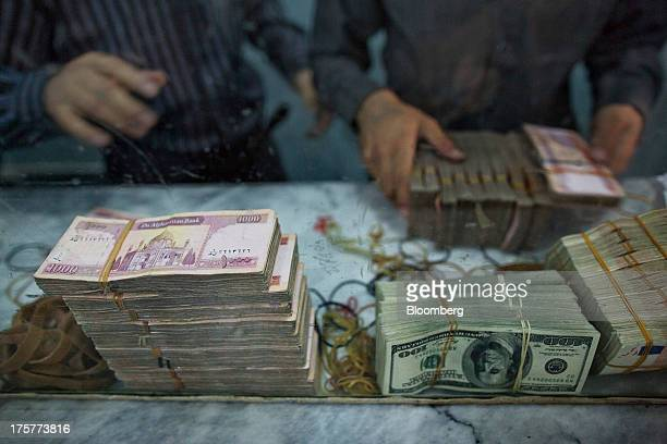 Workers count banknotes of various currencies at the headquarters of the Da Afghanistan Bank Afghanistan's central bank in Kabul Afghanistan on...