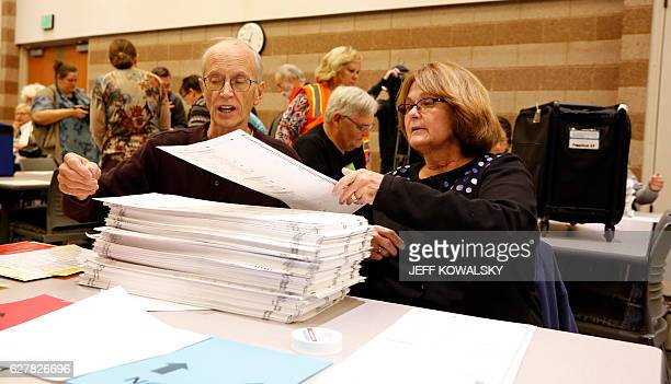 Workers count the number of ballots in the containers before the start of the recount of ballots cast in Oakland County Michigan from the 2016 US...