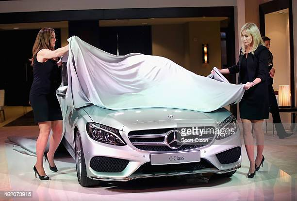 Workers cover a MercedesBenz 2015 C Class before the start of a media event at the North American International Auto Show on January 12 2014 in...