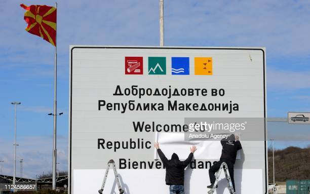 Workers cover over the border sign at the Macedonian-Greek border with the country's new name as; The Republic of North Macedonia, after the Prespa...