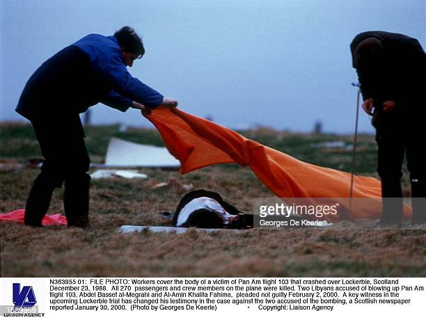 Workers cover the body of a victim of Pan Am flight 103 that crashed over Lockerbie Scotland December 23 1988 All 270 passengers and crew members on...