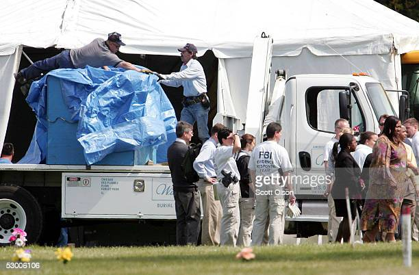 Workers cover the burial vault containing the remains of Emmett Till at Burr Oak Cemetery June 1 2005 in Alsip Illinois The FBI is exhuming the body...