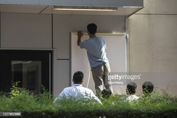 Workers cover up a plaque near the entrance of the vacated U.S. Consulate General in Chengdu, China, on Monday, 27 July 2020. The closure of the U.S....