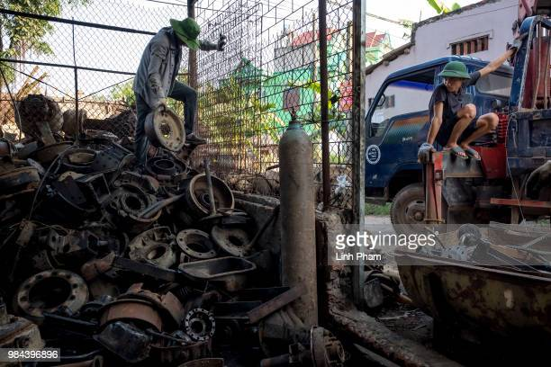 Workers crane the spare parts to shipping truck in order to ship to client at a truck scrapyard on June 7 2018 in Dong Van Village Yen Lac District...