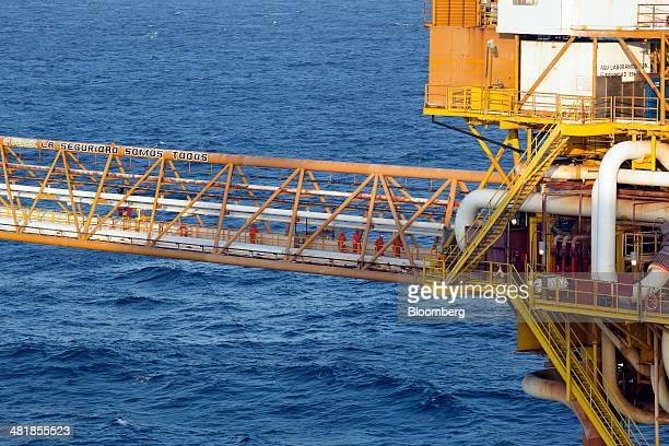 Workers cross a connecting bridge at the Petroleos Mexicanos PolA Platform complex located on the continental shelf in the Gulf of Mexico 70...