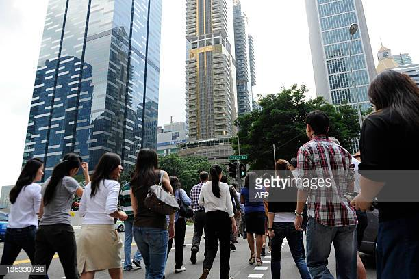 Workers cross the road in the central business district of Singapore on December 9 2011 As European leaders battle to save the euro some Asian...