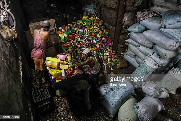 Workers crush and shred plastic waste for recycling in the Dharavi slum area of Mumbai India on Monday Aug 11 2014 Almost a year after Reserve Bank...
