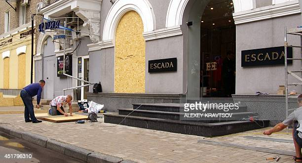 Workers cut boards on July 7, 2014 to protect shop windows in the eastern Ukrainian city of Donetsk. Retreating pro-Russian insurgents dug in on July...