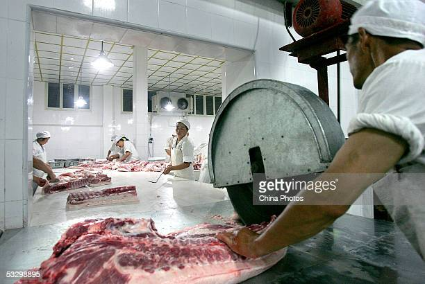 Workers cut pork at the Xuezheng Pork Products Factory on July 28, 2005 in Chongzhou of Sichuan Province, southwest China. China has launched...