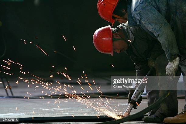 Workers cut steel plates at a Shanghai Baosteel Group factory January 15 2007 in Shanghai China According to state media Baosteel is preparing for an...