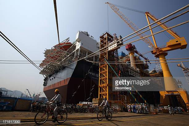 Workers cycle past the Total SA FPSO CLOV a floating production storage and offloading vessel built for the company's Clov oil field project in...