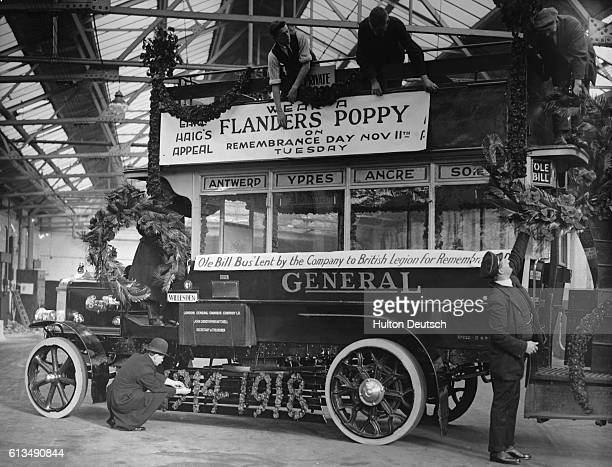 Workers decorate Old Bill, a bus from World War I, with garlands and wreaths for Poppy Day in honor of the World War I Armistice.