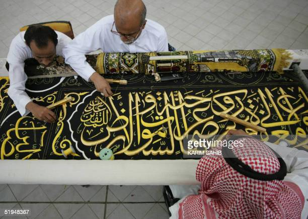 Workers decorate the Kiswa the black pure silk cloth that covers the Kaaba the cube shaped structure at the center of Mecca's Grand Mosque revered by...